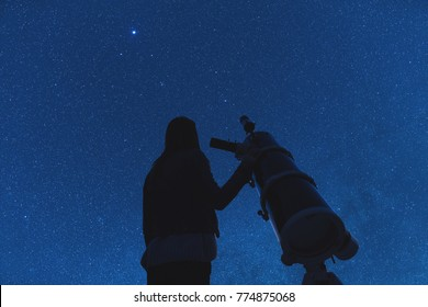 Girl looking at the stars through a telescope. Elements of this image are my work.
