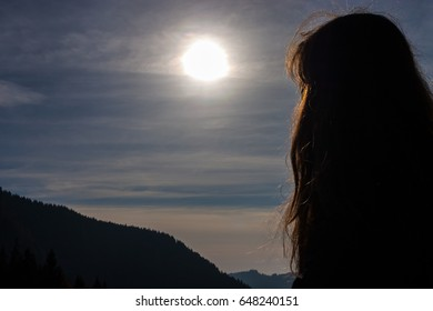 Girl looking at the sun.Valley and mountains in the background.