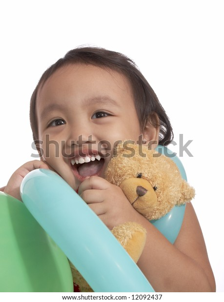 girl looking up with teddy bear and balloon