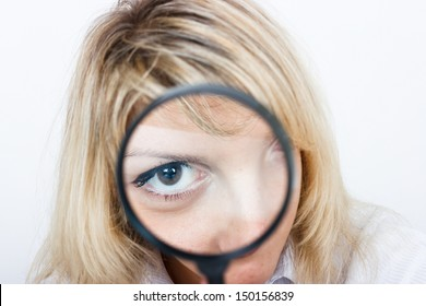 Girl is looking through a magnifying glass