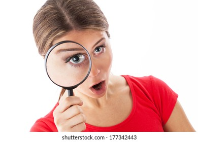 Girl looking through a magnifying glass and looking surprised, isolated on white