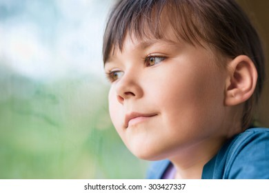 Girl is looking through window while sitting in train, closeup shoot