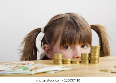 Girl looking at towers of money