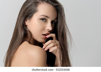 Girl looks around and touches the lips with her hand. She has a clean well-groomed skin and long brown hair. Close-up portrait against a light gray background.