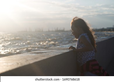 The girl looks at the big waves. On her face is an emotion of delight and surprise. The mouth is open. Hair fluttering in the wind. At sea, a storm. In the backlight at sunset. The man is out of focus
