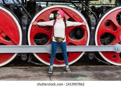 The girl looks at the big wheel train. Vintage steam train stands on the tracks