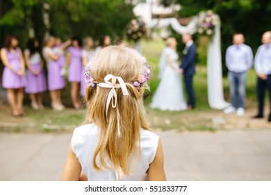 Girl looks at the bride and groom at a wedding ceremony