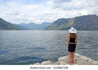 The girl looks at the cruise ship at sea Kotor bay Montenegro