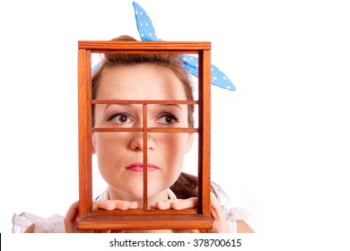 The girl looks in the fake window, white background/ Girl and fake window/ A sad sight