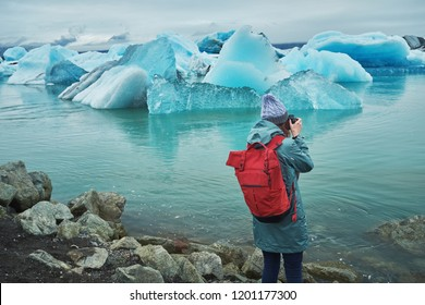 The girl looks at the floating ice. Jokulsarlon Glacier Lagoon. Iceland. Autumn cloudy day.