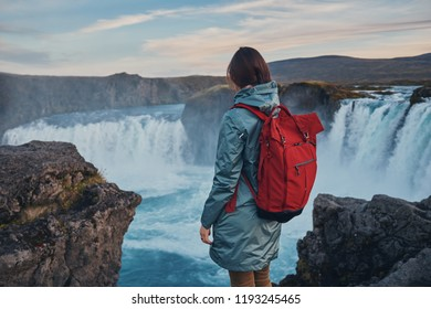 The girl looks at the Godafoss waterfall at sunset. Iceland.