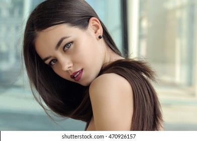 Girl looks in a half-turn. She has long hair and well-groomed skin. Portrait on the background of modern architecture of metal and glass.