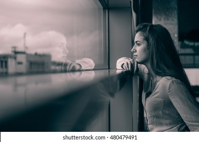 The girl looks at her reflection in the window . a young girl and her long hair