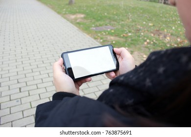 Girl looks at her smartphone walking through the park