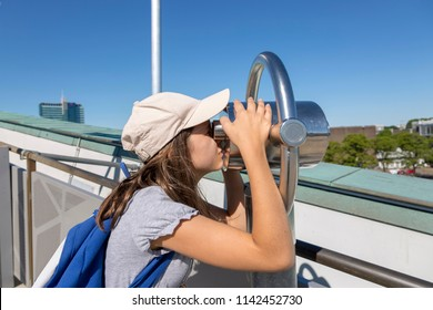 The girl looks with interest at the telescope