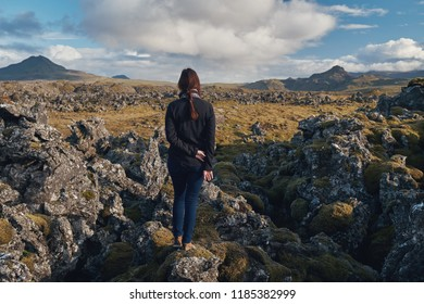 The girl looks at the lava fields overgrown with moss. Iceland.