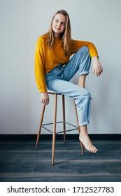 Mädchen sieht links sitzen auf weißem, modernem Stuhl, wobei ein Bein aufsteigt. Schönes Teenagermädchen in gelbem Pullover und blaue Jeans im Inneren mit schwarzem Holzboden. Trendy Casual Outfit.