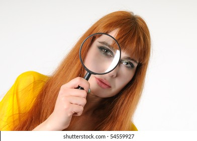 The girl looks in magnifying glass