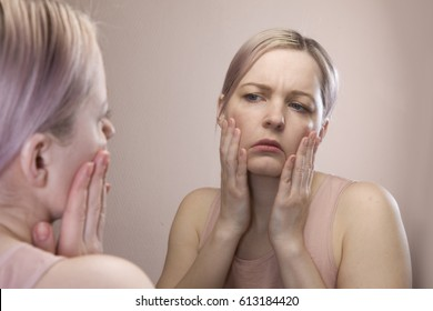 girl looks in the mirror, not pleased with the appearance, pulls the skin. Ugly, aging skin. Allergic to cosmetics, fear of aging, under eye circles, wrinkles. Low self-esteem, dysmorphic disorder.