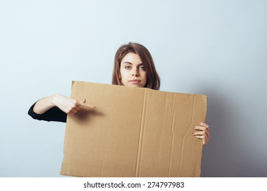 girl looks out from behind a cardboard paper