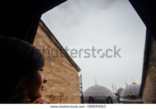 A girl looks out of the window of an old temple. Type in konena temple dome. Soft focus and slight noise of the atmosphere for lifestyle.