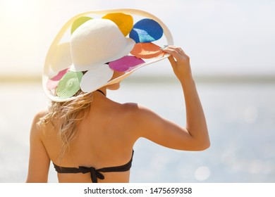 A girl looks at the sea while holding a hat. Young slender woman holds hat  her head with a strong sea wind
