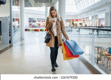 Girl looks at something in her phone walking around the big mall with many stores with shopping bags on her shoulder. Consumerism and lifestyle concept - Image