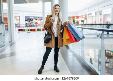 Girl looks at something in her phone standing with shopping bags on her shoulder in the mall. Shopping, sales, Consumerism and lifestyle concept - Image