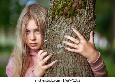 The girl looks sternly out of the tree trunk