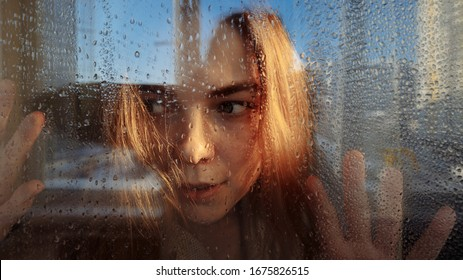 The girl looks suspiciously behind the glass. There are raindrops on the glass. The girl has blond hair and yellow eyes. Hands are pressed to the glass. Outside the window a blue sky.