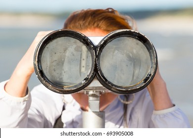 The girl looks through the big binoculars