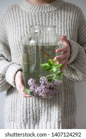 The girl looks through a jar of water and lilacs. Reflections