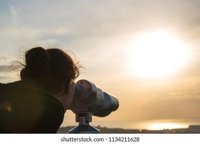 A girl looks through panoramic binoculars on a viewing platform