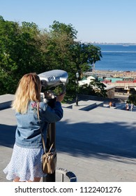 A girl looks through the tower viewer (telescope) to the sights of the city