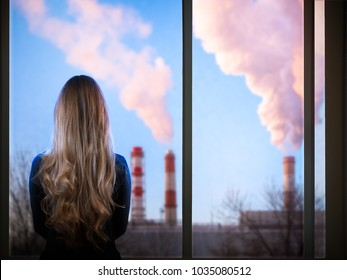 The girl looks through the window at the district heating pipe. Concept - ecology of the city, environment, harmful emissions into the atmosphere