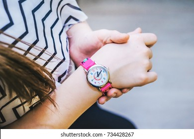 Girl looks time on her pink kids watch.