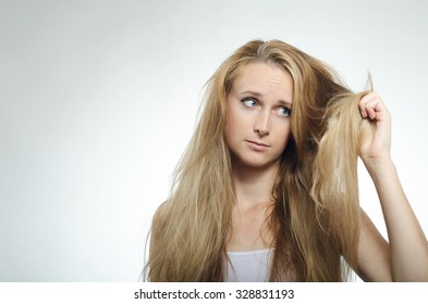 Girl looks at the tips of the cross-section of hair