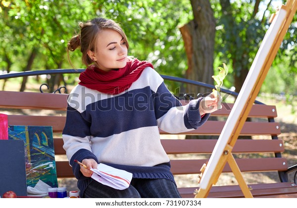 A girl looks at a twig on the background of an easel