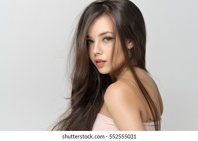 Girl looks uncertainly over her shoulder. She has a clean well-groomed skin and long brown hair. Close-up portrait against a light gray background.