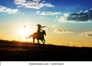 Girl loses hat while riding horse at sunset