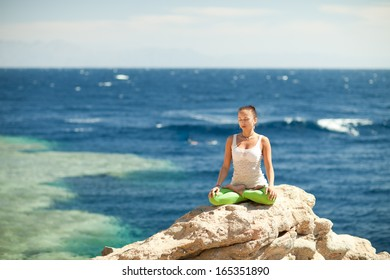 girl in lotus position on the rock by the sea