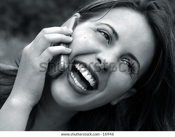 Girl loughing while in a phonecall.