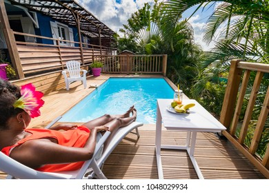 Girl is lounging on chair next to swimming pool, at Diamant, Martinique the 09th of March 2018