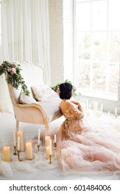 Girl in a luxurious pink dress sitting near the couch. Before her a large window