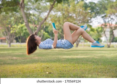 Girl lying in the air with a book