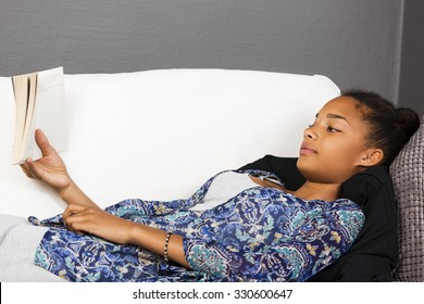 Girl lying in a couch reading a book.