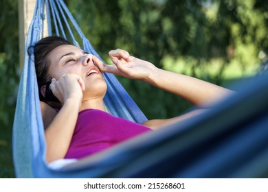 girl lying in a hammock, talking on the phone and piking her nose
