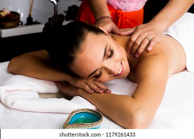 The girl is lying in the masseur's office. Masseur doing a relaxing massage with oils