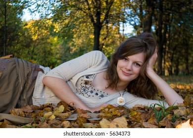 Girl lying on autumn leaves in park
