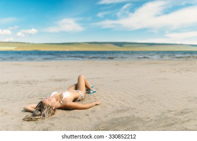 girl lying on the beach and sunbathing . against the background of the sea